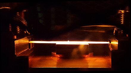 Grafitová páska (žiariaca tyčinka), ktorá ohrieva termopotovoltaický článok, ktorý je pod ním. Kredit: Luis M. Pazos Outόn, UC Berkeley